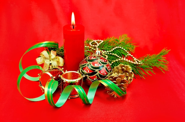 Red burning candle, christmas tree decorations, hand bell with bow, drum, cones against red silk