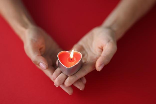 Красная горящая свеча в форме сердца в женских руках на красном фоне одиночества в любви