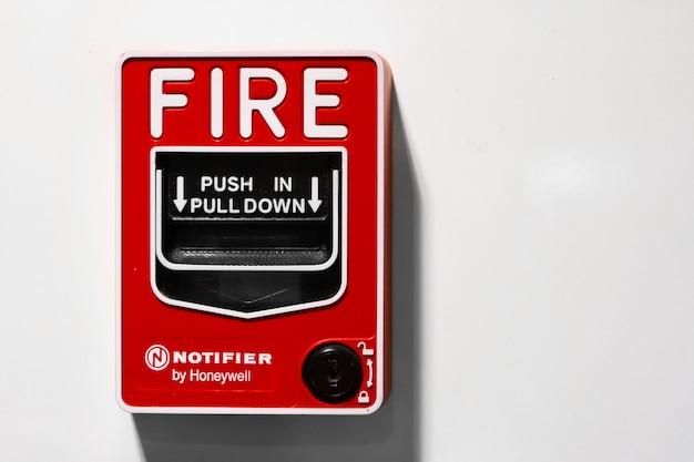 壁に赤いボタンのハンドブレーキ火災警報。