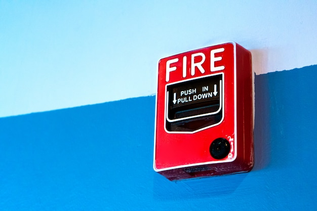 Red button handbrake fire alarm on the wall.