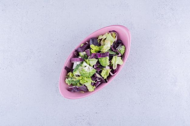 대리석 바탕에 타원형 그릇에 붉은 양배추와 브로콜리 샐러드. 고품질 사진