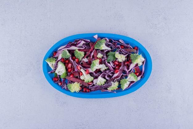 붉은 양배추와 브로콜리 샐러드는 대리석 배경에 석류 가자미와 섞입니다. 고품질 사진