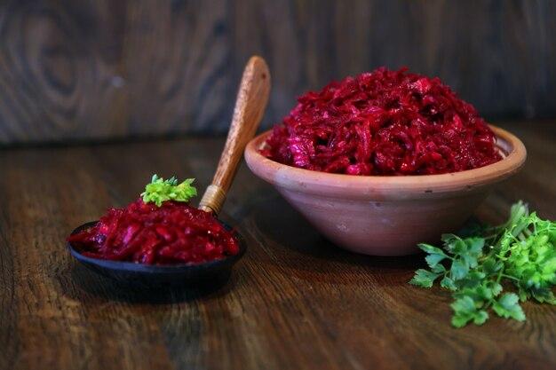 붉은 양배추와 당근 신선한 샐러드, 비건 샐러드 - 소박한 나무 배경에 있는 맛있고 맛있는 홈메이드 음식, 식사용 비타민 콕테일 요리. 파 또는 마늘 믹스