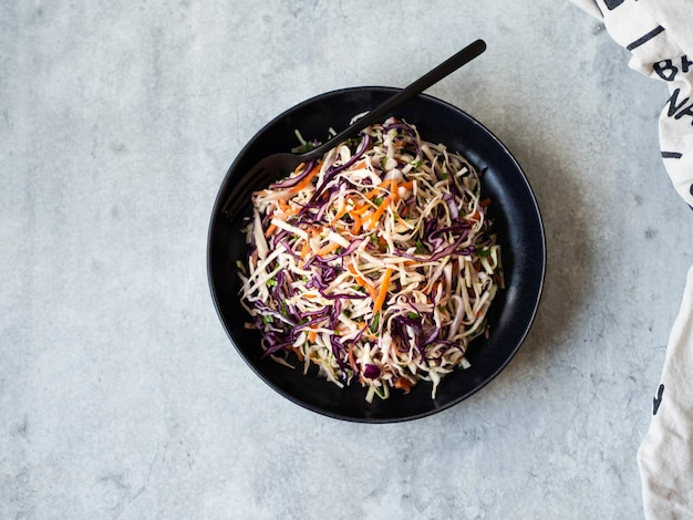 Red cabbage, carrot, cabbage coleslaw salad on black plate on grey background. top view