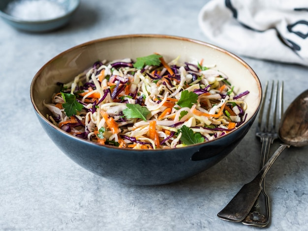 Red cabbage, carrot, cabbage coleslaw salad in blue bowl on grey background.