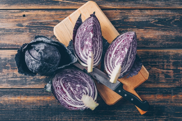 Red cabbage in a cutting board with sliced cabbage and knife top view on a dark wooden background