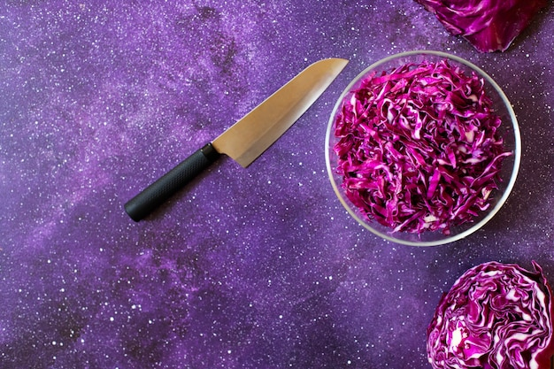 Red cabbage fresh salad in a glass bowl on a dark purple background. vegetarian healthy food. top view, copy space