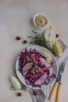 레몬과 올리브 오일 소스를 곁들인 붉은 양배추, 배, 헤이즐넛 샐러드.
