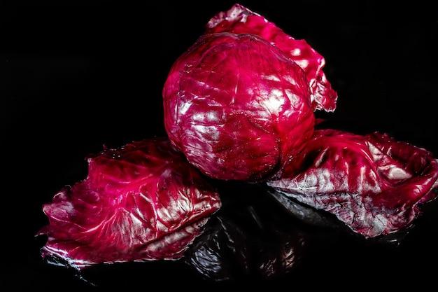 赤キャベツ。黒の背景に生野菜。前景。ベジタリアンフード。スペースをコピーします。
