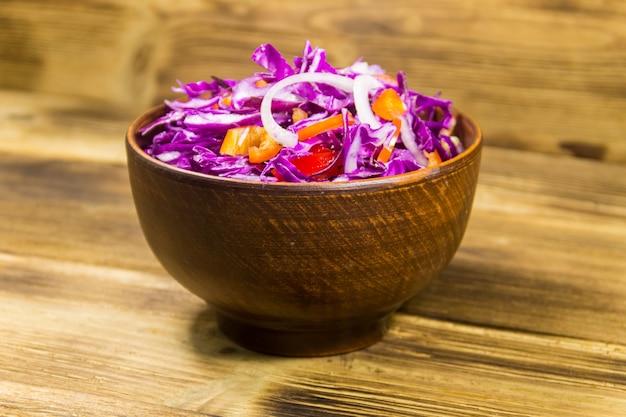 木製のテーブルの上のセラミックボウルに赤キャベツのサラダ