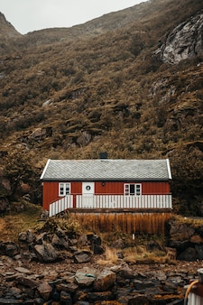 Red cabin near mountains and rocks