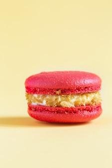 Красный торт macaron или миндальное печенье на желтой стене. разноцветное миндальное печенье. французский макарун торт