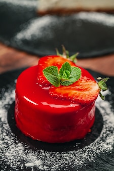 Red cake with cream on white plate on wooden table