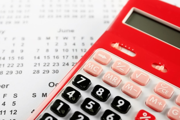 Red calculator on calendar, closeup