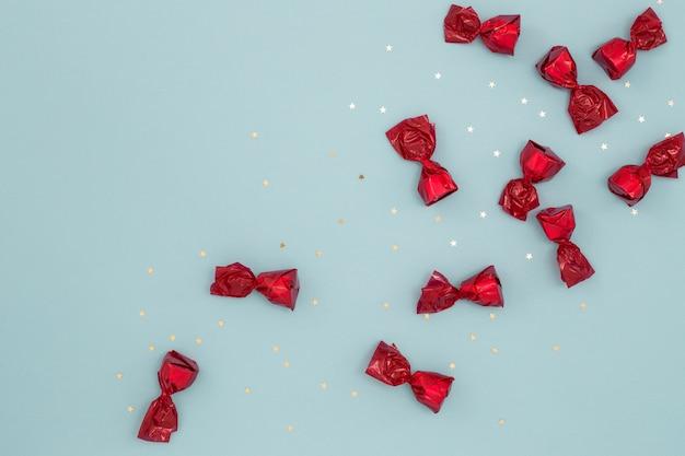 Красные конфеты и золотое конфетти на синей поверхности
