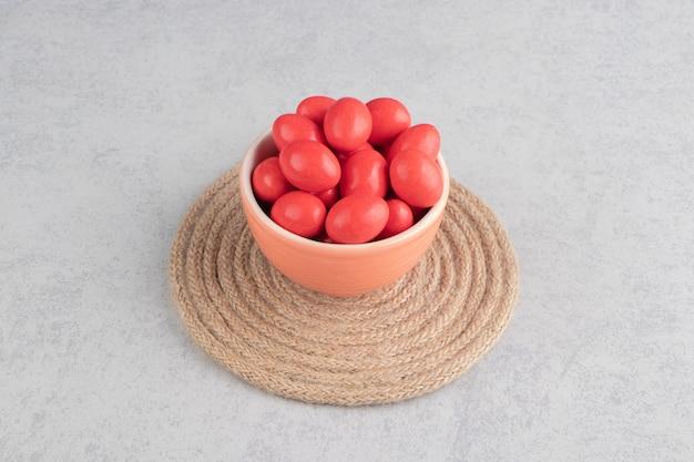 大理石の表面のトリベットのカップに赤いキャンディー