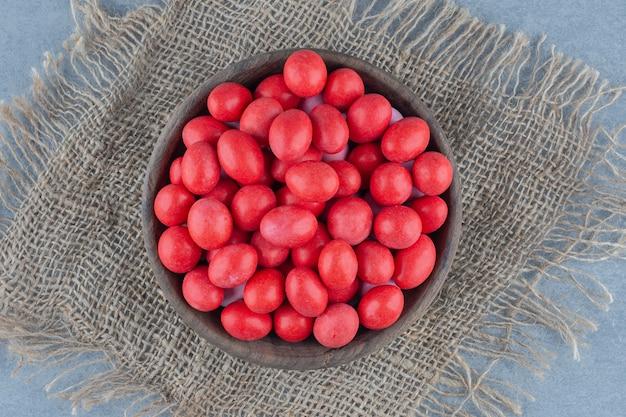 Красные конфеты в чашке на подставке, на мраморном столе.