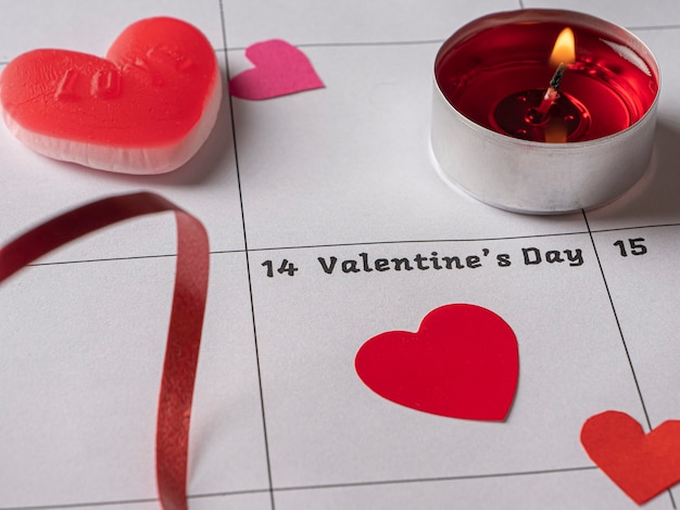 Red candle hearts and ribbon on white calendar with valentine's day