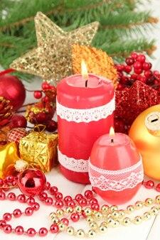 밝은 배경에 크리스마스 장식이 있는 빨간 촛불