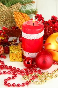 밝은 표면에 크리스마스 장식이 있는 빨간 촛불