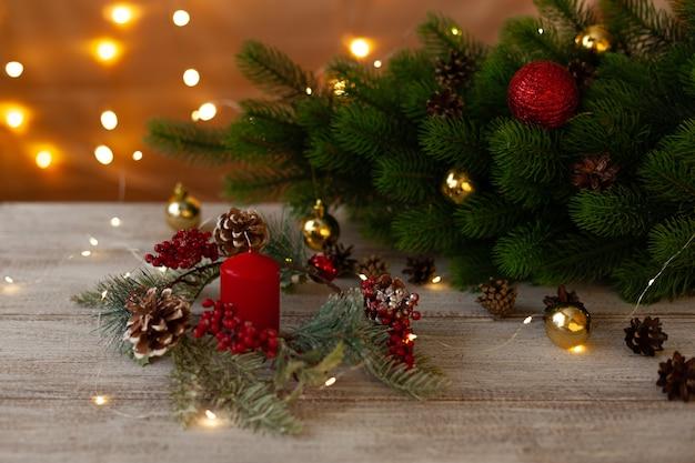 赤いろうそく、クリスマスツリーの近くの花輪