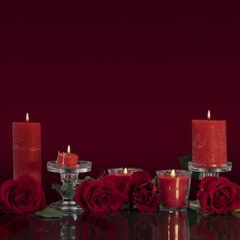 유리 촛대에 있는 빨간 양초는 거울에 있는 장미로 둘러싸인 밤에 타오른다