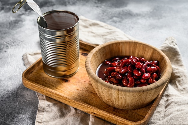 竹ボウルに赤豆の缶詰。灰色の背景。上面図。