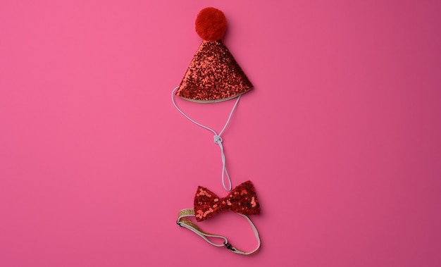 Red cap and a butterfly on the neck with sequins on a pink background. festive costume