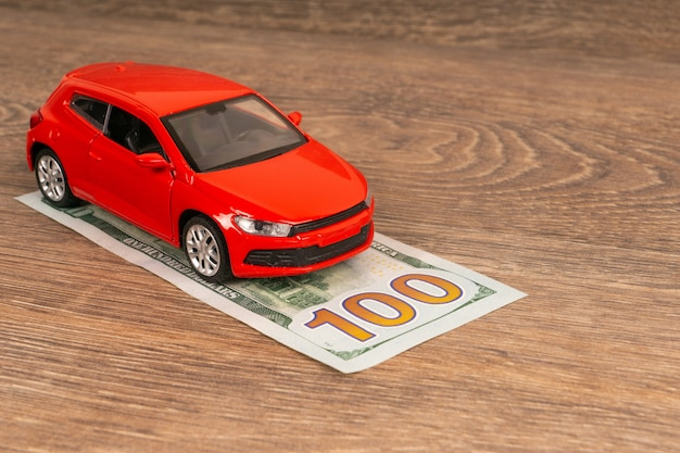 Red car and 100 dollars banknote, insurance concept