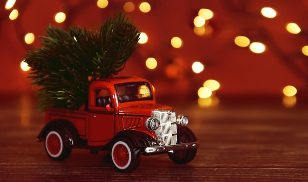 Red car carrying a christmas fir tree on the snow background.