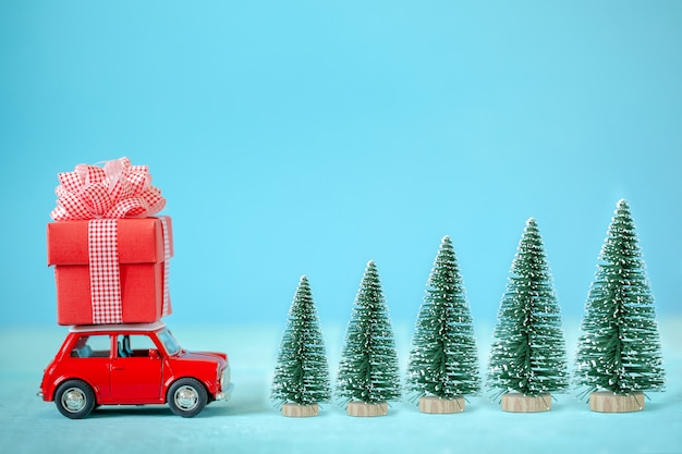 Red car carrying on roof a gift box  and christmas tree. christmas and new year concept