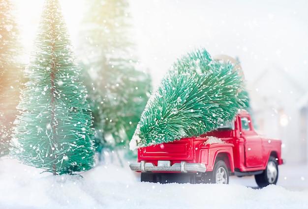 숲에서 크리스마스 트리를 운전하는 빨간 자동차