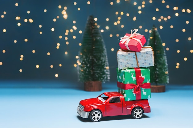 A red car in a forest carries christmas gifts.