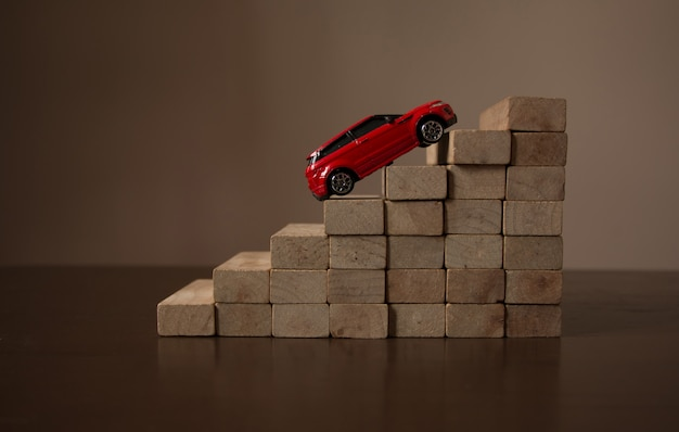 Red car going up on roll stair step of wooden staircase stack, natural bright light background