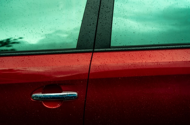 Red car is washing with water. auto care business. car with drops of water after cleaning with water. car cleaning before waxing service. vehicle cleaning service.