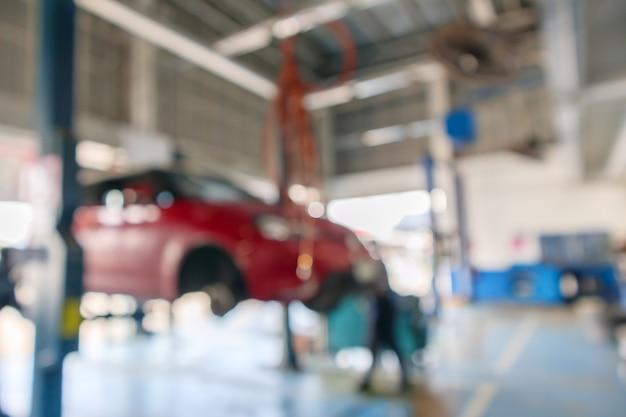 자동차 서비스 센터의 유지 보수 스테이션에서 빨간 자동차 리프트 추상적 인 배경 흐림