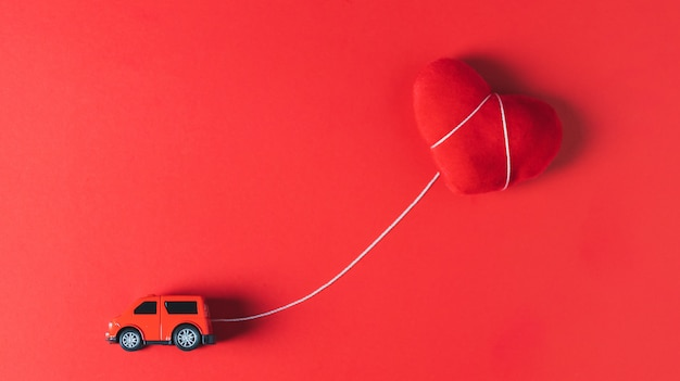 A red car model towing a red heart pillow on a red backdrop, concept, valentine's day theme