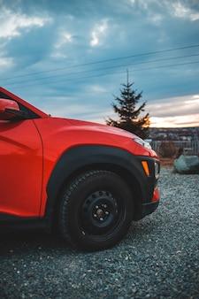 昼間の間に灰色のアスファルト道路に赤い車