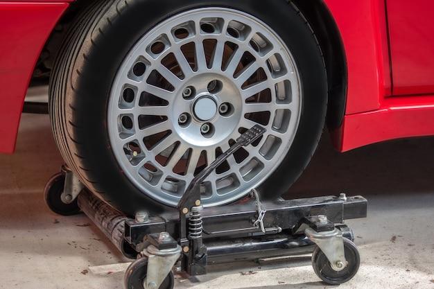 Красный автомобиль на гидравлических колесных коньках для удобного передвижения в сервисе