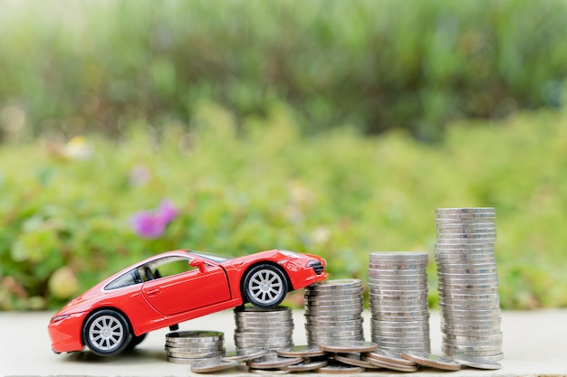흐린 녹색 자연 배경에 동전 더미에 빨간 차. 돈과 투자 개념을 절약합니다.