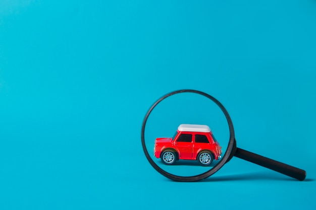 Красный автомобиль заглянул с увеличительным стеклом на синем фоне. технический осмотр и поиск машины