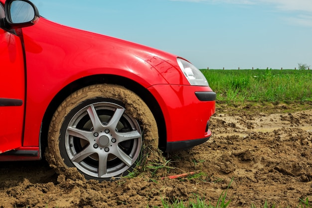 Red car's wheel stuck in the mud
