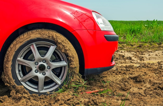 The red car stuck in the mud. can not fall out of the mud