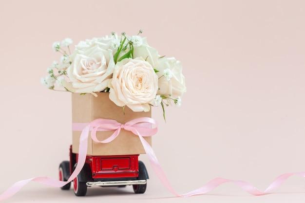 Красная машина с подарочной коробкой цветов роз на крыше на розовом фоне. с днем святого валентина, день матери, 8 марта, концепция праздничной карты всемирного женского дня, доставка цветов.