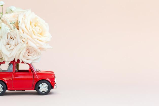 Красный автомобиль с цветами роз на крыше на розовом фоне. с днем святого валентина, день матери, 8 марта, концепция праздничной карты всемирного женского дня, доставка цветов.