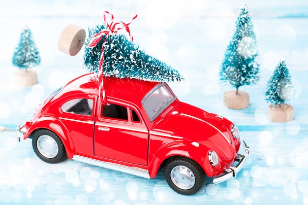 Red car with christmas tree in miniature evergreen forest