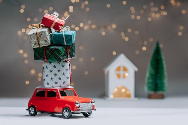 지붕에 선물을 가진 빨간 차입니다. 집과 나무의 배경. 크리스마스와 새 해의 주제에 개념.