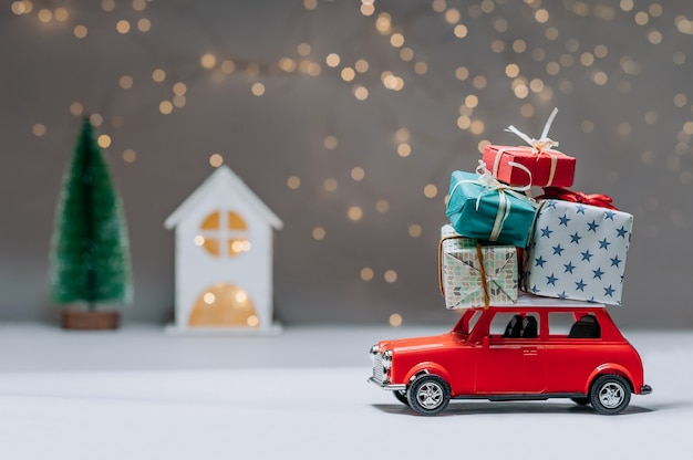 Red car with gifts on the roof. against the background of a house and a christmas tree. concept on the theme of christmas and new year.