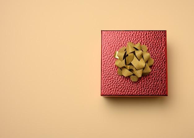 Красная картонная коробка, перевязанная шелковой красной лентой на бежевой поверхности, вид сверху