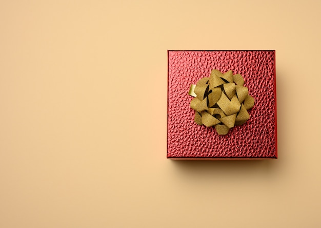 Red cardboard box tied with a silk red ribbon on a beige surface, top view
